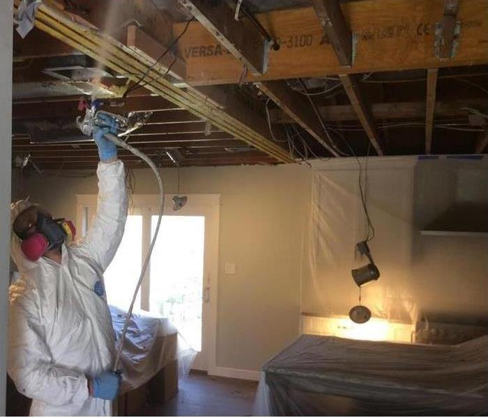 SERVPRO employee applying sealer to ceiling beams after fire damage cleanup