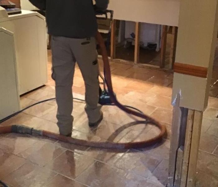 SERVPRO employee with black shirt and khaki pants using professional steam cleaning tool